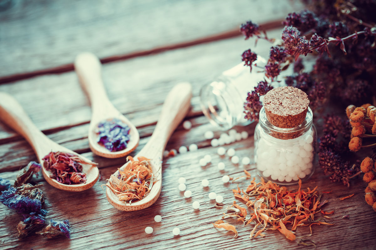 Bottle of white homeopathy globules, wooden spoons and dry healthy herbs. Selective focus. Retro styled.